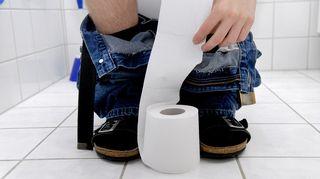 Miehestä vessanpöntöllä näkyvät jalat ja kädet, joilla vetää vessapaperia rullasta.
