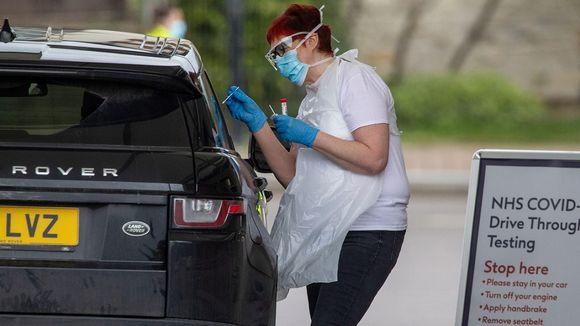 Maskiin, suojalaseihin, kumikäsineisiin ja muoviesiliinaan pukeutunut nainen ottaa auton ikkunan kautta näytettä kuljettajalta.