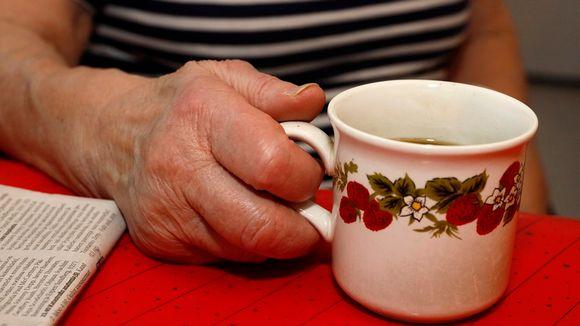 Ikääntyneen naisen käsi pitelee mansikkakuvioista kahvikuppia. Pöydällä näkyy myös sanomalehden kulma.