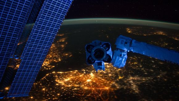 Satelliitin robottivarren takana näkyy maapallon kaartuva pinta, jota täplittävät miljoonat valot.