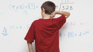 Poika katselee taululla olevia matemaattisia kaavoja