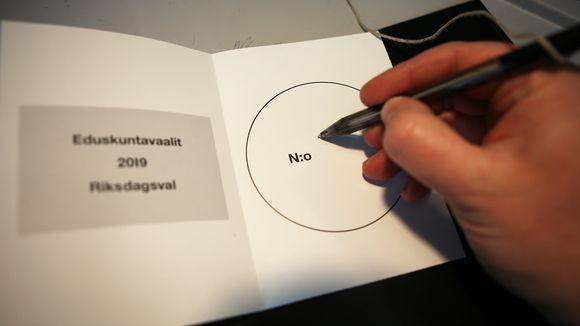 Mies kirjoittaa numeroa äänestyslappuun.