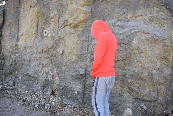 Poika seisoo ulkona huppu päänsä yllä.
