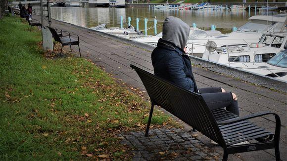 Nuori istuu penkillä.