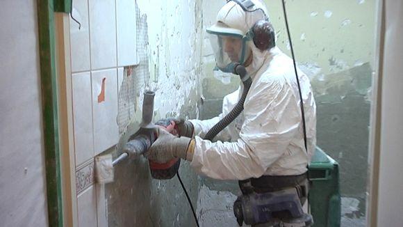 Työmies poraa kaakelia seinästä. Putkiremontissa uudistetaan yleensä koko vessa.
