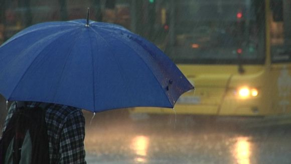 Mies on sateenvarjon alla kaatosateessa