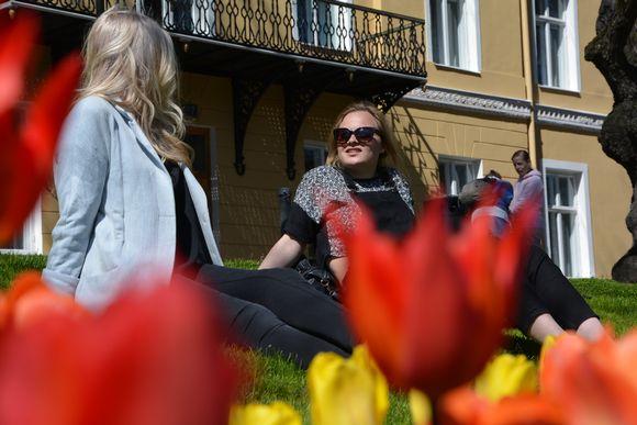 Naiset istuvat nurmikolla jokirannassa.