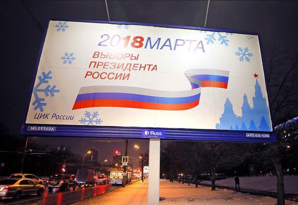 Kuva tienvarren mainostaulusta, jossa kerrotaan maaliskuun presidentinvaaleista. Kuvan vasemmassa reunassa autot ajavat tiellä. On ilta ja pimeää.