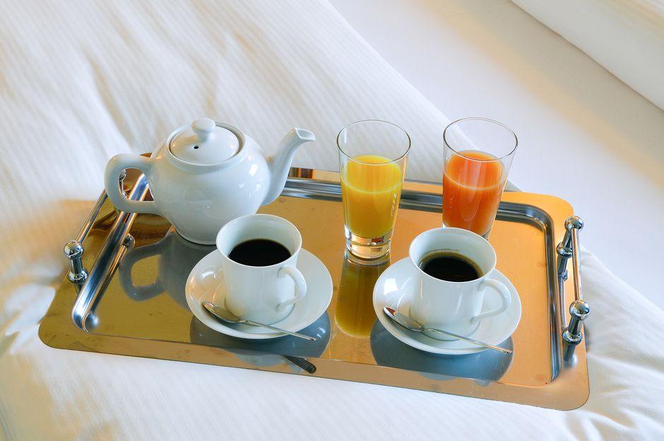 Kahvitarjotin hotellin sängyllä.