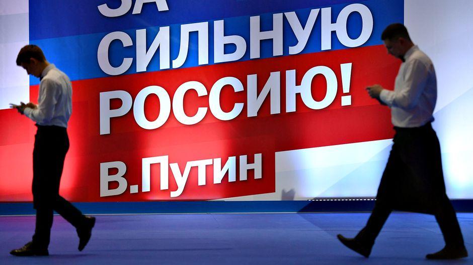 Kaksi mieshahmoa kävelee vaalimainoksen ohi Vladimir Putinin kampanjatoimistossa. Vaalimainoksessa lukee isolla