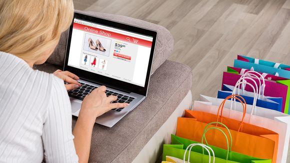 Nainen selaa verkkokaupan tuotteita kannettavalla tietokoneella.