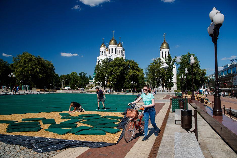 Työntekijä asettelee aukioille vihreitä muovimattoja. Taustalla seisoo valkoinen kirkko, jossa on kullanväriset kupolit.