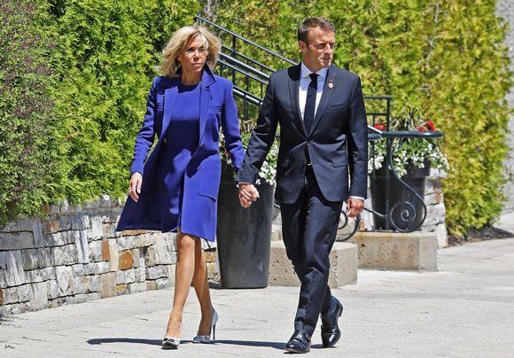 Emmanuel ja Brigitte Macron käsi kädessä.