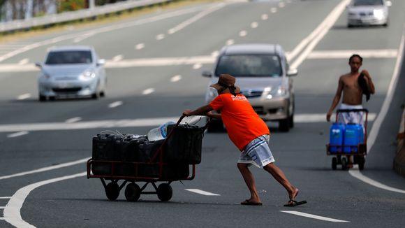 Filippiiniläinen työntää vesikanistereita kärryssä.