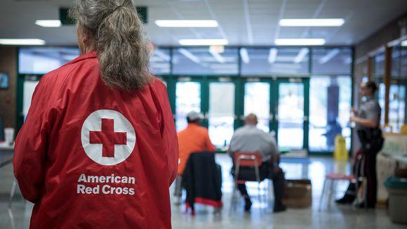 Punaisen Ristin naistyöntekijä seisoo evakuointikeskuksen salissa selin kameraan, päällään Punaisen Ristin logolla varustettu punainen takki. Taustalla näkyy kaksi penkeillä istuvaa miestä ja seisova nainen.