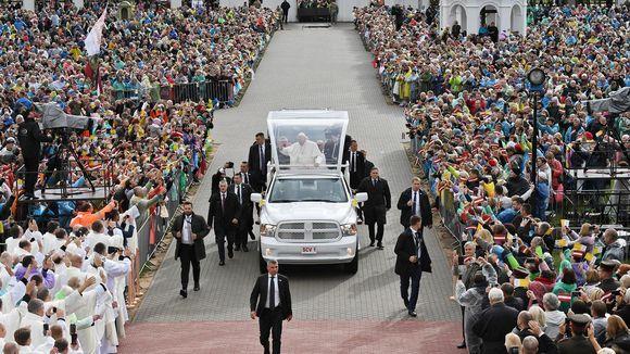 Paavi avoautossa väkijoukon keskellä.