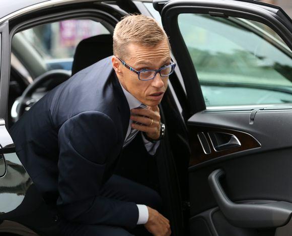 Alexander Stubb korjaa kravattiaan noustessaan auton takapenkiltä.