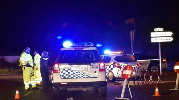 Kaksi poliisiautoa on parkkeerattuna keskelle tietä, siniset vilkut välkkyvät. Tiellä seisoo kaksi miestä kirkkaankeltaisissa haalariasuissa ja univormupukuinen nainen. Kuvan oikeassa laidassa näkyy tieviitta Sant Llorençiin.