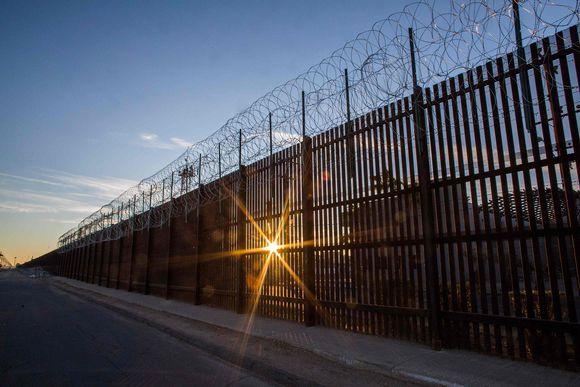Aurinko nousee Yhdysvaltain ja Meksikon välisen raja-aidan välistä 30. joulukuuta 2018.