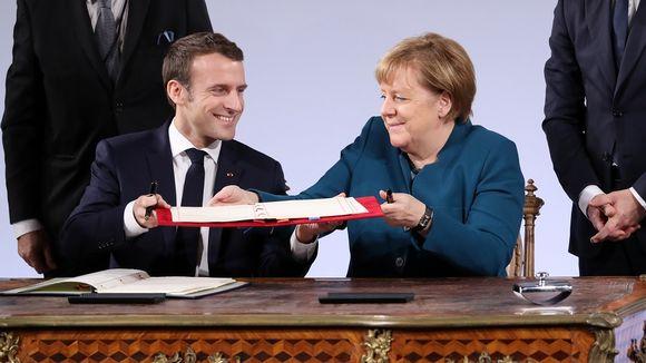 Macron ja Merkel istuvat kirjoituspöydän takana ja pitävät asiakirjaa kädessään.