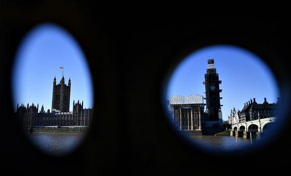 Binokulaarinen jalustan läpi kuvattu maisema Lontoossa. Vasemmassa aukossa näkyvät parlamentin tornit ja oikeassa aukossa Big Ben.