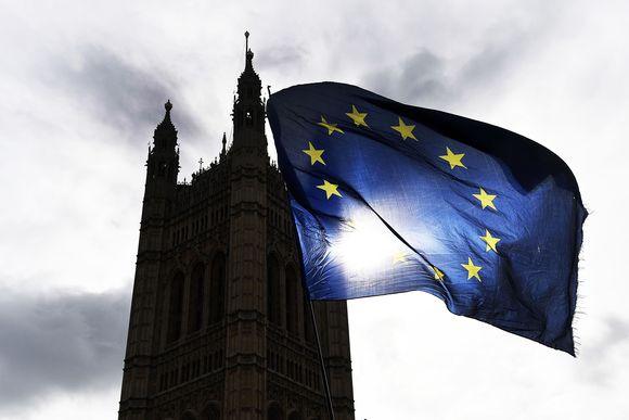 Britannian parlamenttitalon tornin silhuetti EU-lipun taustalla.