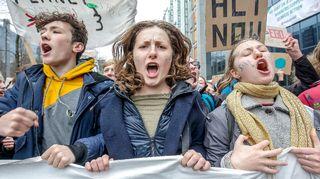 Kolme nuorta mielenosoituksessa, taustalla mielenosoituskylttejä.