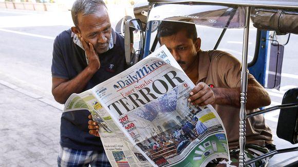 Kaksi srilankalaista lukevat sanomalehteä kadulla.