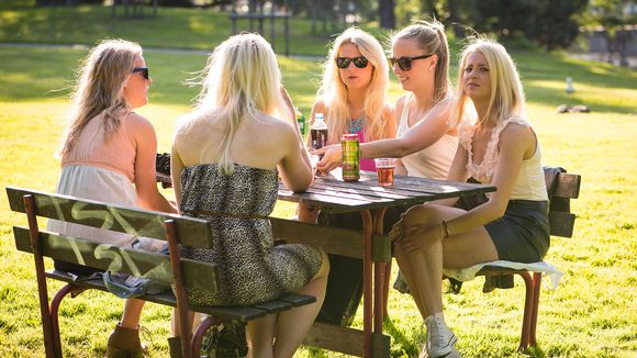 Naisia puistossa pöydänääressä kesällä.