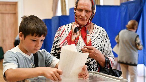 Vanhempi nainen antaa nuoren pojan laittaa hänen äänestyslomakkeensa vaaliuurnaan Kievissä