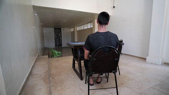 Mies tuolilla kuvattuna takaa.