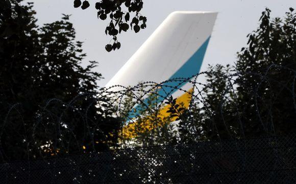 Lentokoneen pyrstö puiden takaa kuvattuna.