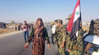 Siviilit tervehtivät Syyrian hallinnon joukkoja Tal Tamr -kaupungissa 14.10.
