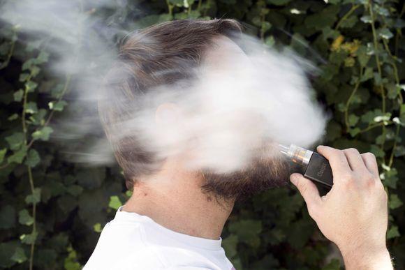 Mies polttaasähkötupakkaa.