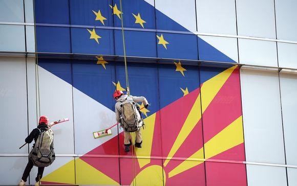 Työntekijät puhdistavat EU:n ja Pohjois-Makedonian lipuilla koristettua ikkunaa.