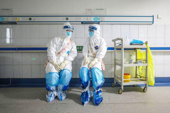 Suojapukuihin pukeutuneet työntekijät keskustelevat sairaalassa Wuhanissa.