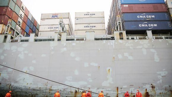 Suojamaskiin pukeutuneet työntekijät työskentelevät satamassa Kiinan Qingdaossa.