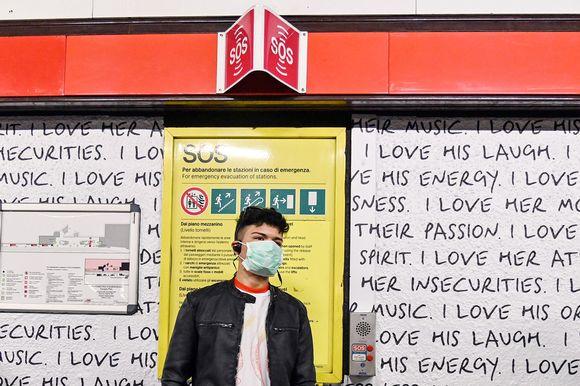 Suojamaskiin pukeutunut mies odottaa metroa Milanossa.