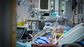 Potilas makaa sairaalavuoteessa hengitysmkoneessa, sängyn ympärillä useita sairaalalaitteita. Kasvot pixelöity. Koronapotilas hengityskoneessa milanolaisessa sairaalassa maaliskuun lopussa.