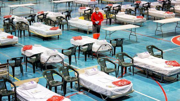 Punaisen ristin työntekijä valmistelee väliaikaissairaalan vuodepaikkoja Barcelonassa.