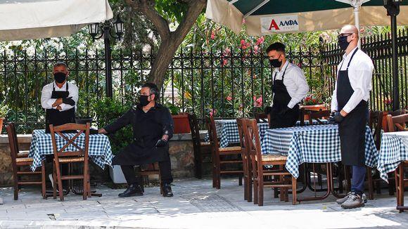 Ateenassa kasvomaskeihin suojautuneet tarjoilijat odottavat asiakkaita.