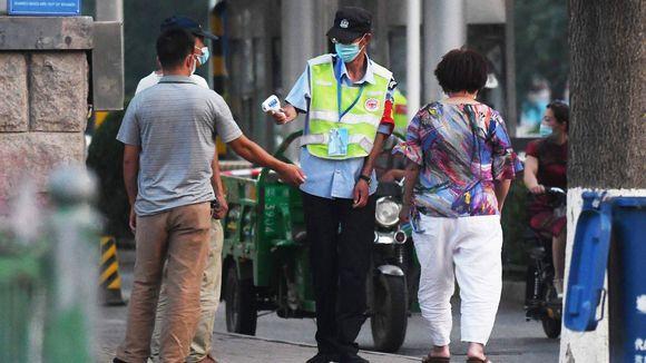 Ihmisilta mitattiin lämpö Xinfadin tukkumarketin edustalla perjantaina.