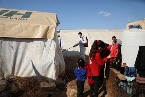 Vapaaehtoistyöntekijä suihkutti Syyrian Idlibissä sijaitsevan pakolaisleirin telttoihin ja yleisiin tiloihin desinfiointiainetta maaliskuun loppupuolella varotoimenpiteenä koronavirusta vastaan.
