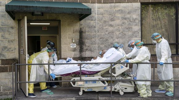 Hoitohenkilökunta siirtää potilasta sairaalan edustalla.