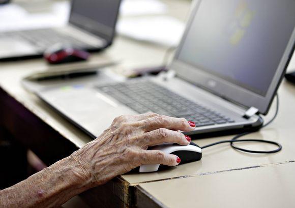 Eläkeläisnainen käyttää tietokonetta.