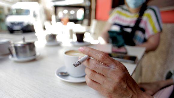 Nainen polttaa tupakkaa kahvilan pöydässä.