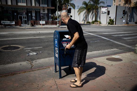 Mies laittaa kirjeen postilaatikkoon.