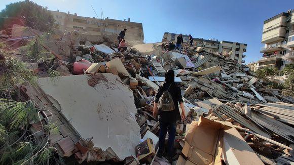 Ihmisiä sortuneen rakennuksen raunioilla.