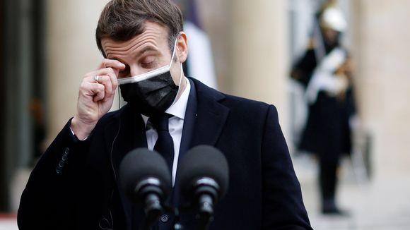 Kasvomaskiin pukeutunut Emmanuel Macron hieroo silmäänsä tiedotustilaisuudessa.