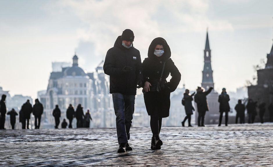 Ihmisiä suojautuneena kasvomaskeihin kävelyllä Moskovassa.